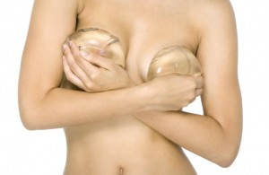 Nude woman covering breasts with breast implants, cropped view